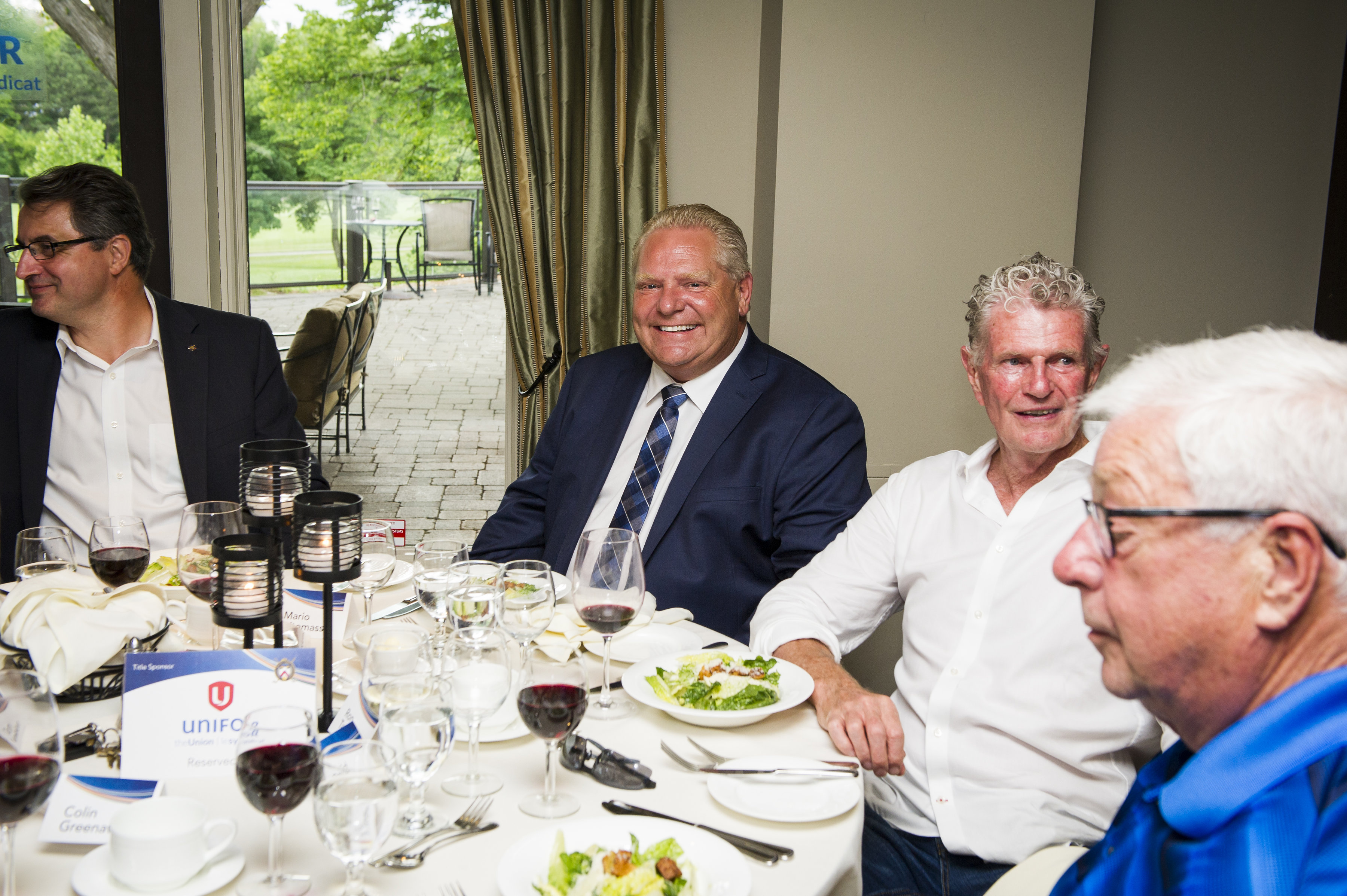 Doug Ford, centre, and Toronto Police Inspector Ron Taverner, white shirt, second from right, at the Markland Woods Golf Club last June.